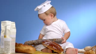 child with bread on blue wall in cook hat