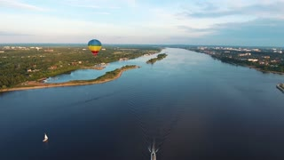 Colorful hot air balloon flying near river