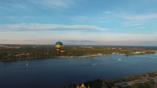 Colorful hot air balloon flying over the river