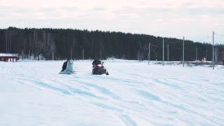 Couple in warm clothing sledding on snow