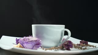 Cup of tea with flowers rotation isolated on black