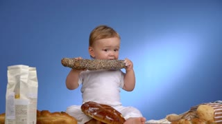 cute baby with bread on blue wall eating a loaf