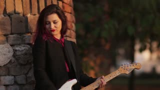 Fashion girl with guitar playing outside
