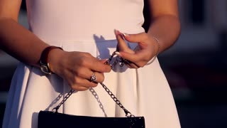 Fashionable woman with a black bag in her hands