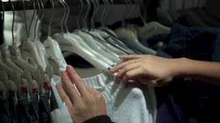 female hands choosing clothes on a rack