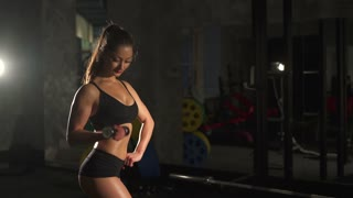 Fitness woman with dumbbells in dark gym