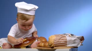funny baby baker playing with bread