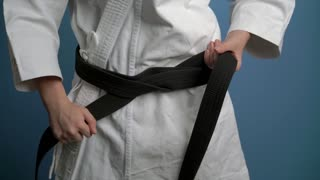 girl putting on black karate belt