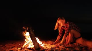 Girl resting and bored by camp fire at night