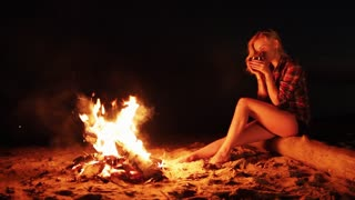 Girl resting drinking coffee by camp fire at night