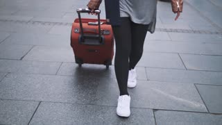 Girl tourist walking with luggage on the street
