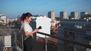 Girl Using A Smartphone On A Balcony