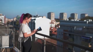 Girl Using device On A Balcony
