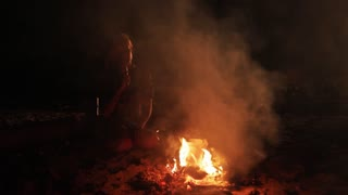 Girl vaping by camp fire at night