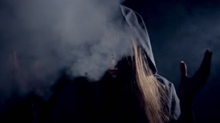 Halloween scary girl as a witch in smoke