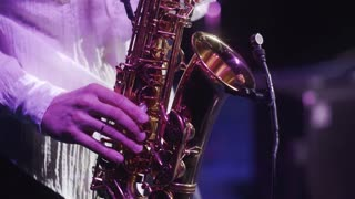 handsome musician plays jazz at saxophone in gig