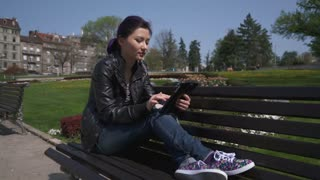 happy asian student girl working with a tablet pc in a green park