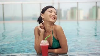 happy smiling girl drinking cocktail in pool