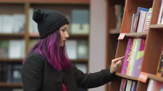 happy student girl taking book from shelf in library