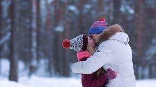 Happy winter travel couple under snowfall