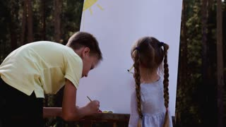 Little girl painting color on easel