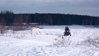 Man shooting young couple on snowmobile