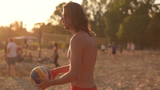 Muscular shirtless young man playing volleyball