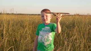 naughty boy in wheat field running with a toy plane