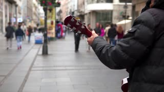 Playing guitar on blurred urban background