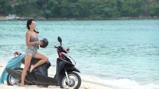 Pretty Woman putting on a Helmet on the beach