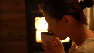 Pretty woman warming up with hot tea at fireplace