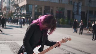 Sexy woman with electric guitar in the street