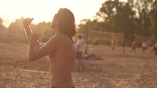 shirtless young man playing volleyball on the beach