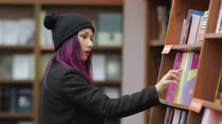 student girl taking book from shelf in library