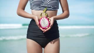 Tanned slim woman holding dragon fruit in hands