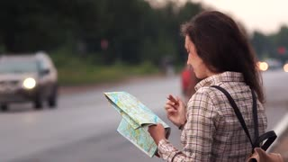 Traveler woman searching a route in map