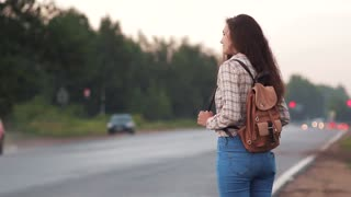 Traveler woman with a suitcase catching a car