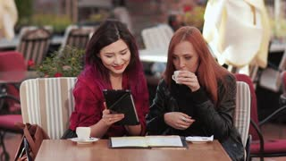 Two frends girls in cafe using tablet pc
