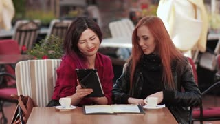 Two frends girls laughting in cafe using tablet pc