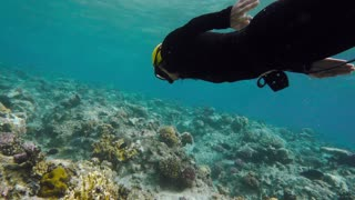A girl free diving On a coral reef