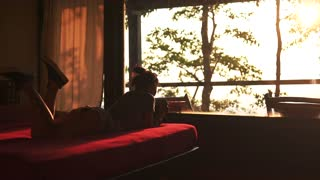 A girl on a bed in bedroom at sunset with camera