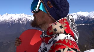 A snowboarder close up walking in the mountains