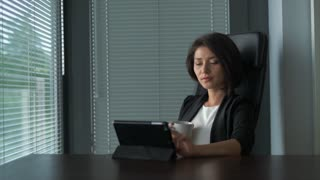Business woman wearing suit, working with tablet pc