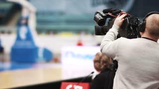 Camera operator filming live basketball game