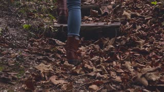 Feet walking upstairs on fall leaves in forest