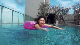 Girl with pink ring buoy in swimming pool