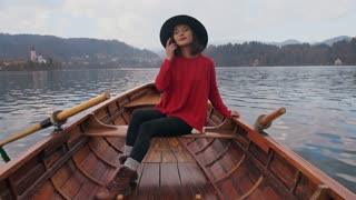 happy woman enjoying nature in a wooden boat