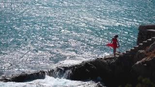Lonely girl in red dress at ocean cliff beach