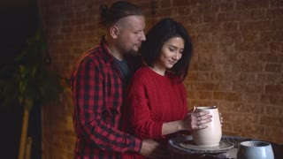 Man and a woman making clay jug on potter's wheel