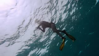 Pretty Free diver exploring coral reef in sea
